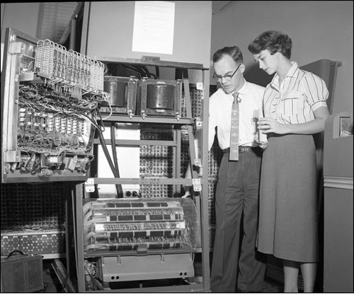 Employees using an old IBM computer