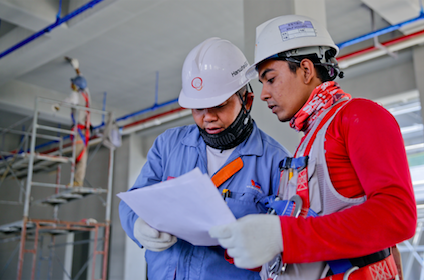 two men wearing hard hats look at a white paper together